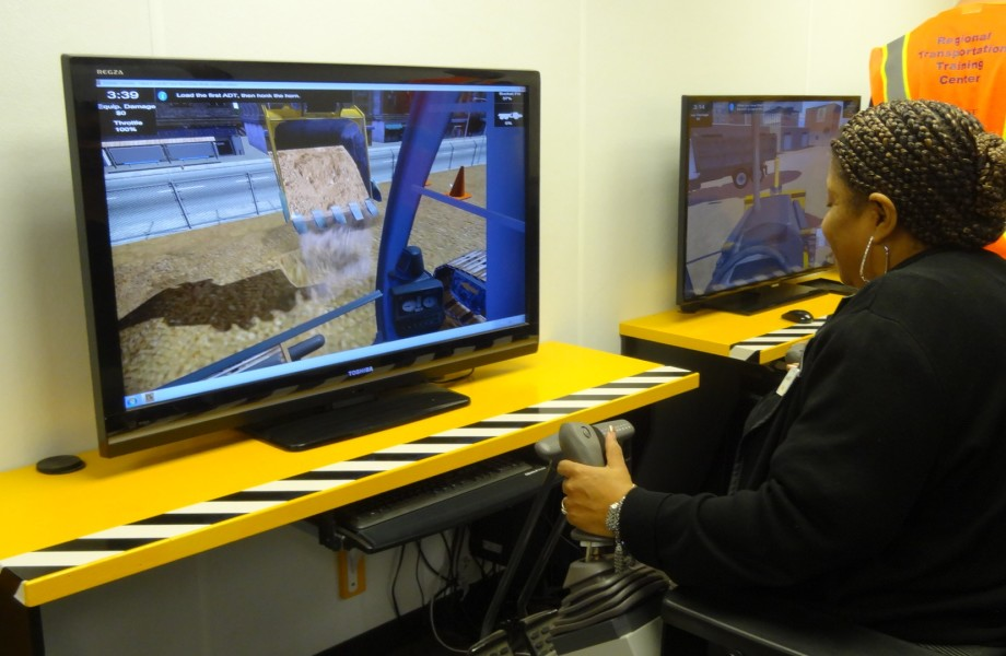 A woman at a computer simulates driving a backhoe.