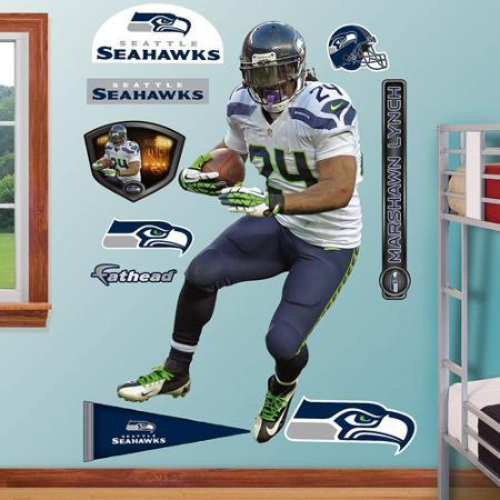 A wall is full of Seattle Seahawks stickers, including a life-size player and logos