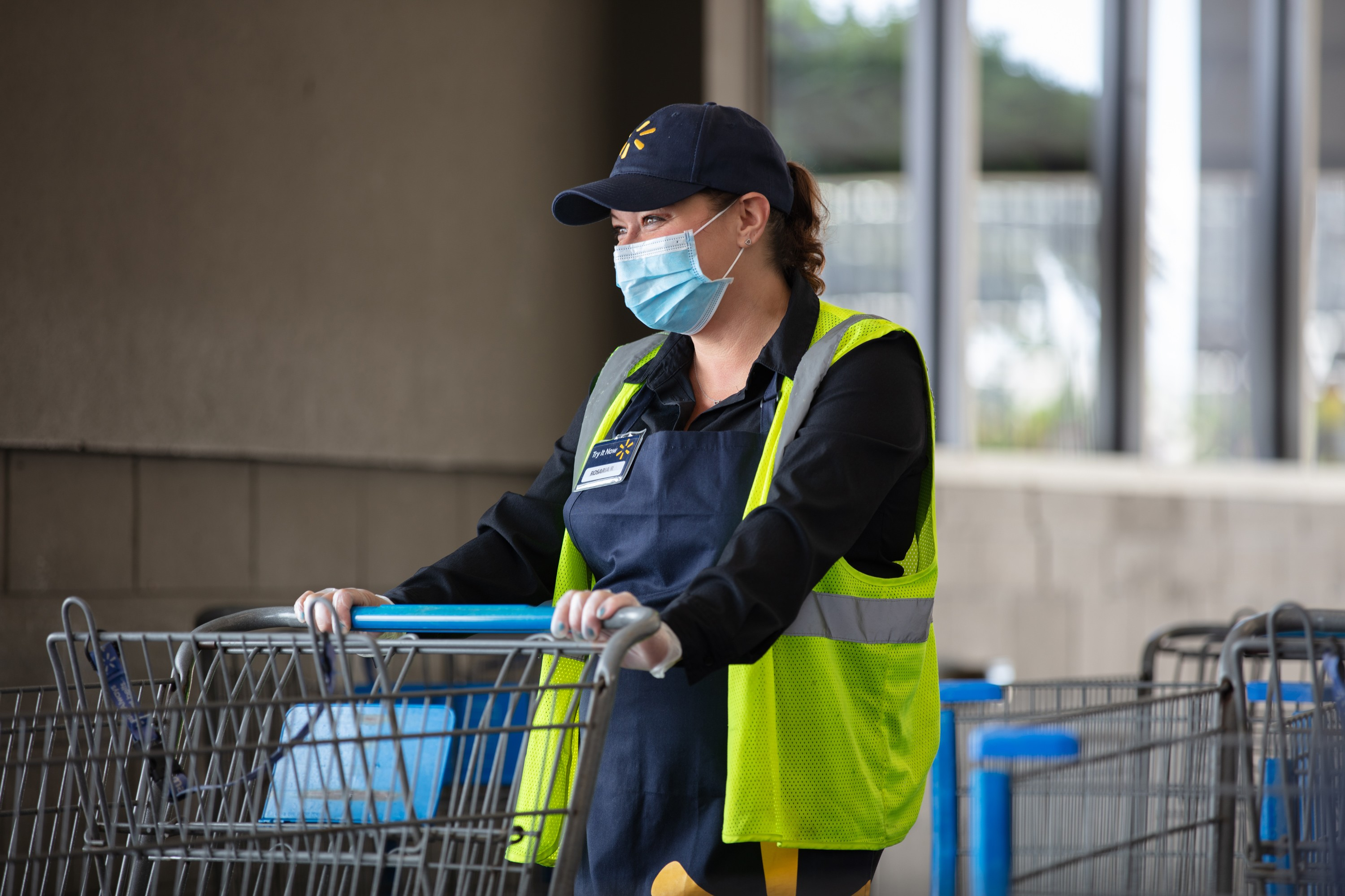 An associate wears a mask while moving carts