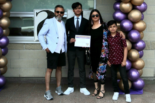 Shahpoor Amiri poses with his wife and two sons to celebrate his oldest son's Grade 8 graduation.