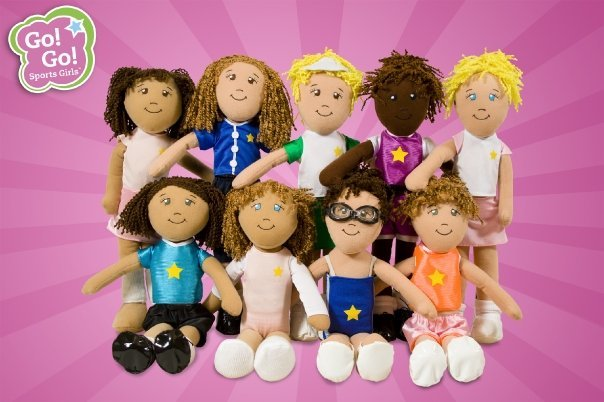 Nine cloth Go Go Sports Girls dolls of different ethnicity, outfits and hair colors and styles sit and stand together. All dolls have a yellow star on their outfits.