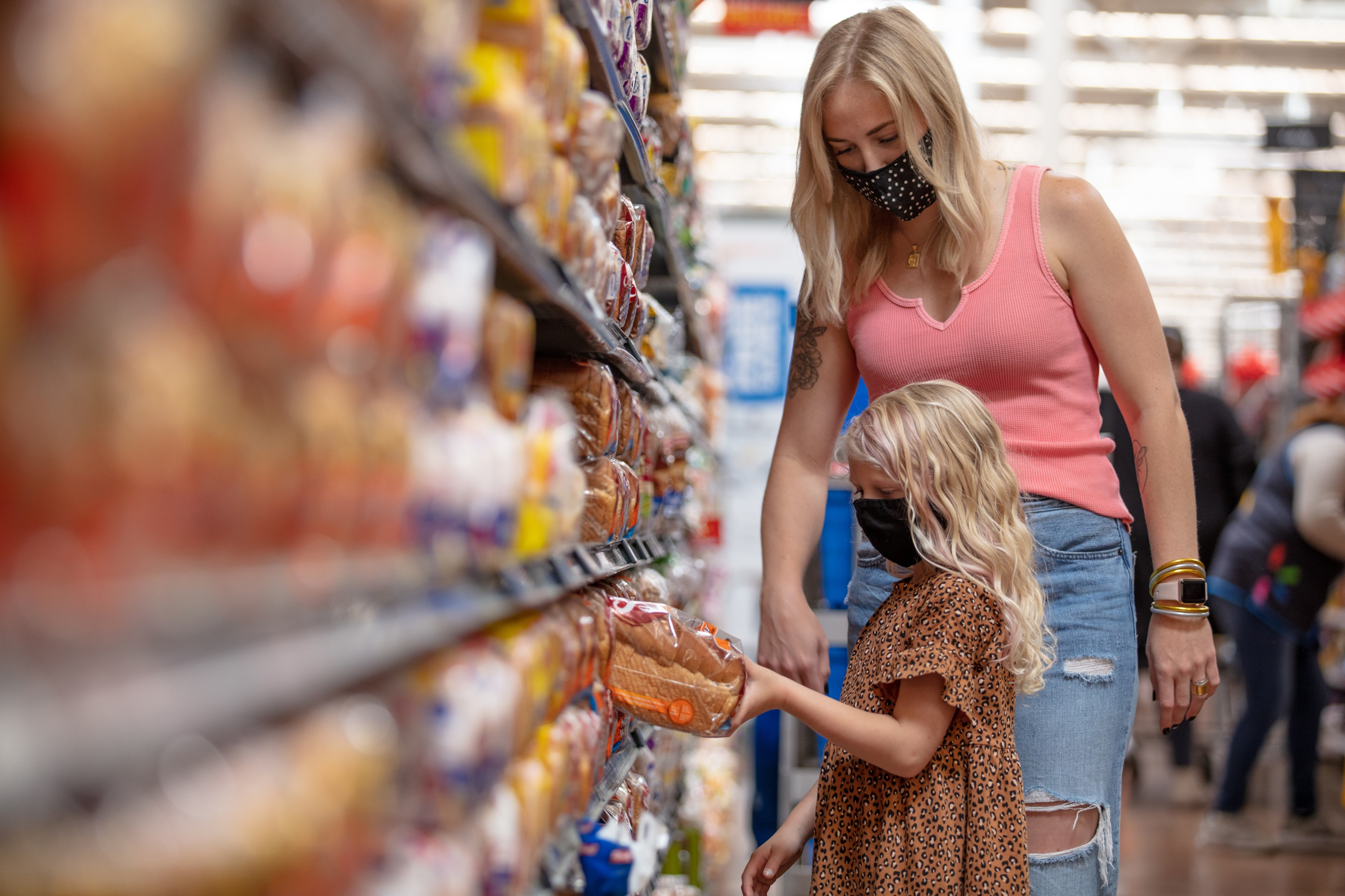 Walmart customers, Calley Williams and her daughter, wear masks while shopping for bread