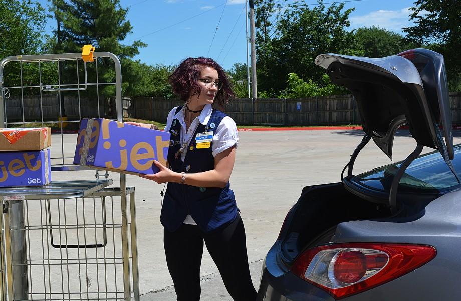 Female associate loading a Jet box in the trunk of a car