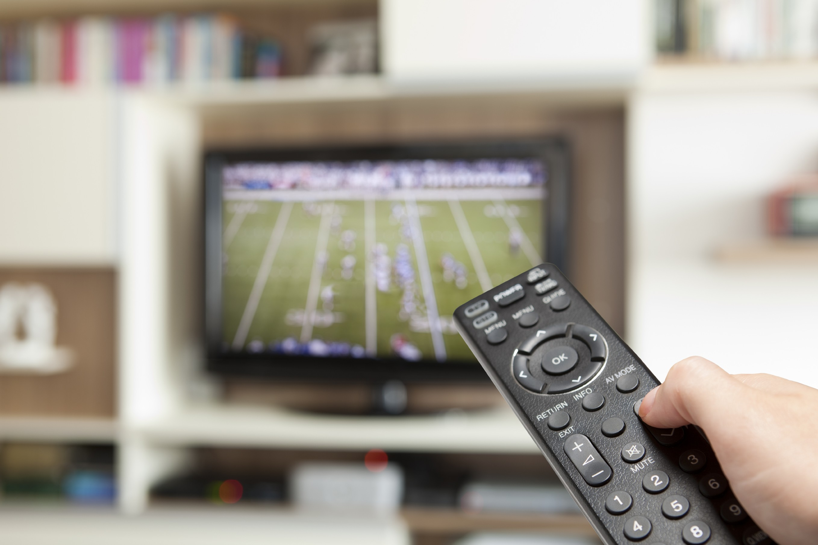 A black television remote is pointed at a tv in the distance which has a football game on.
