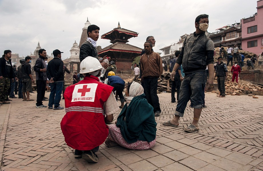 A support aid wearing a red Nepal Red Cross Society vest sits beside a woman on a brick road in front of a crowd of men and rubble.