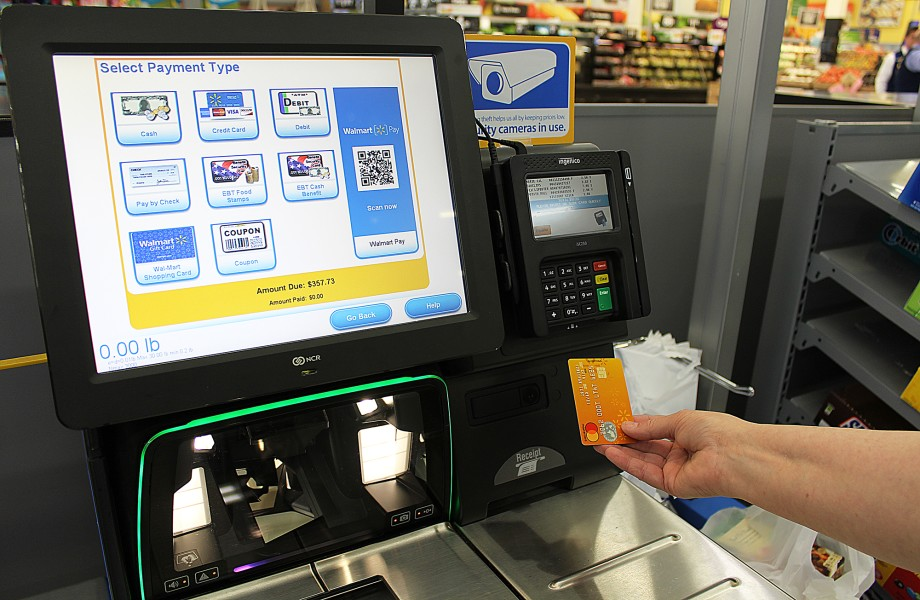 A customer prepares to insert their Walmart credit card into a checkout card reader.