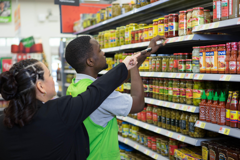 Associate Pamela Twiner helps an associate in the food aisle