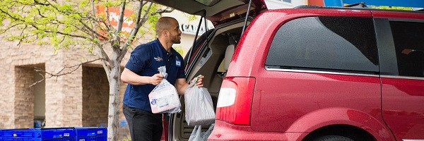An associate loads groceries in to a customer's red van at a Walmart store