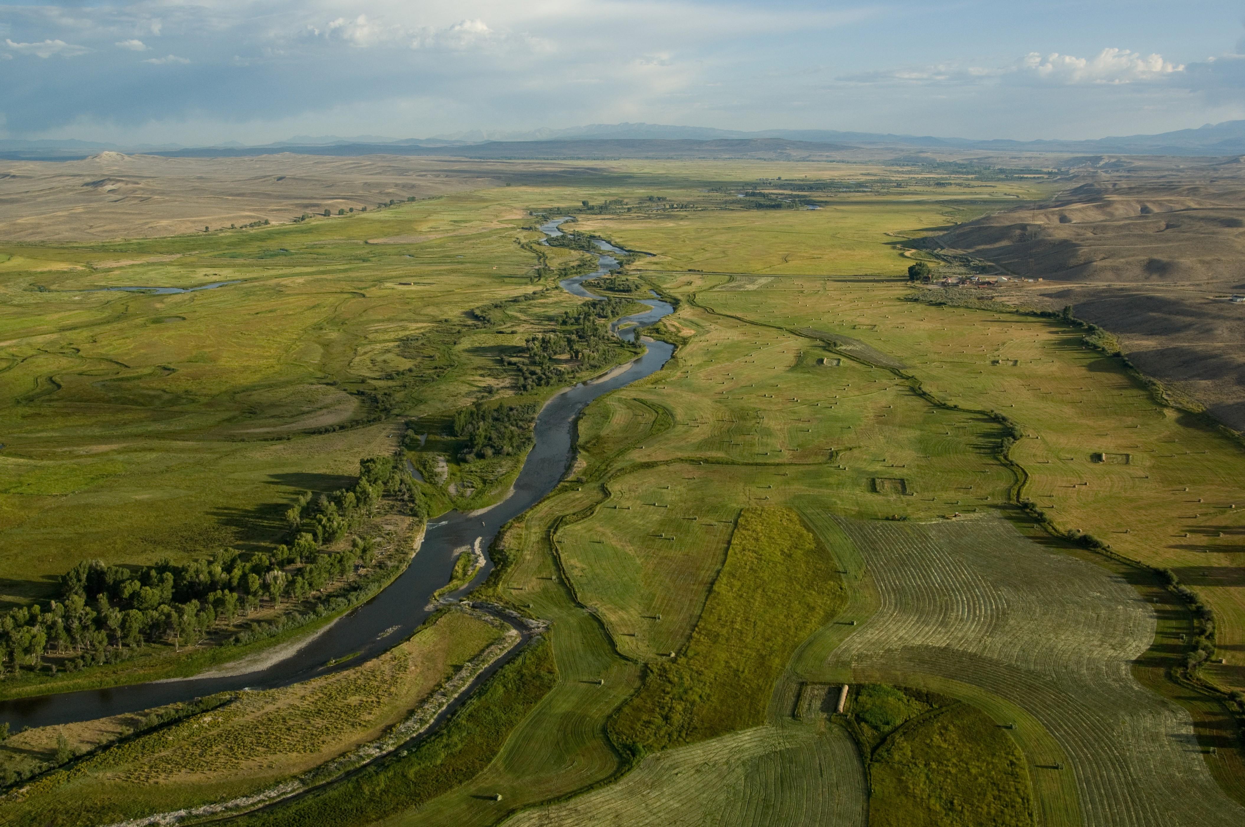 A small river runs through farm land