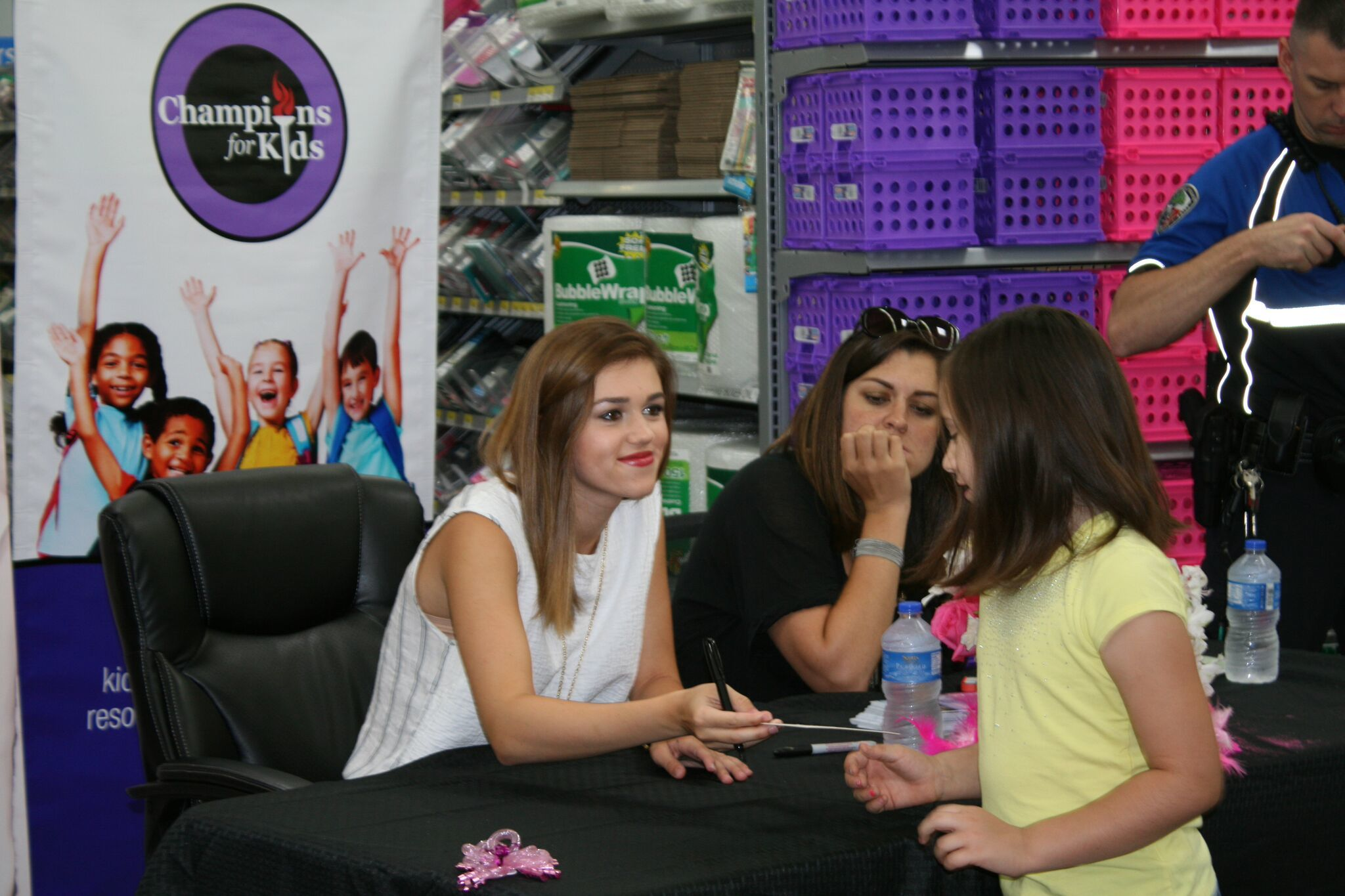Sadie Robertson is seated in front of a Champions for Kids banner and is handing a young girl a piece of paper.