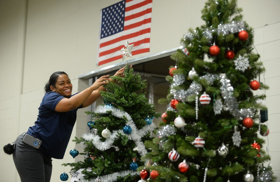 An associate places a star on a Christmas tree