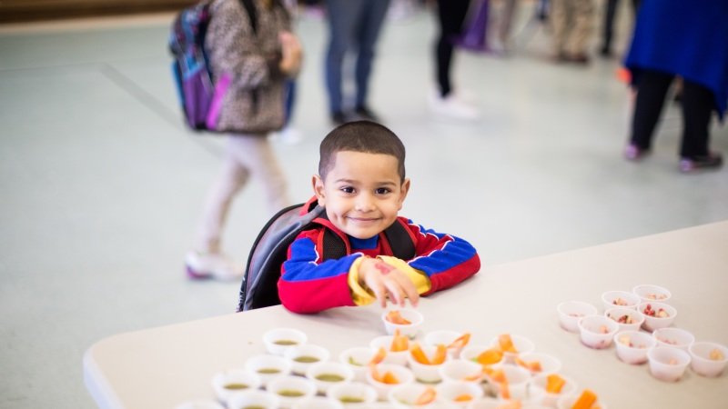 A child smiles while selecting a snack