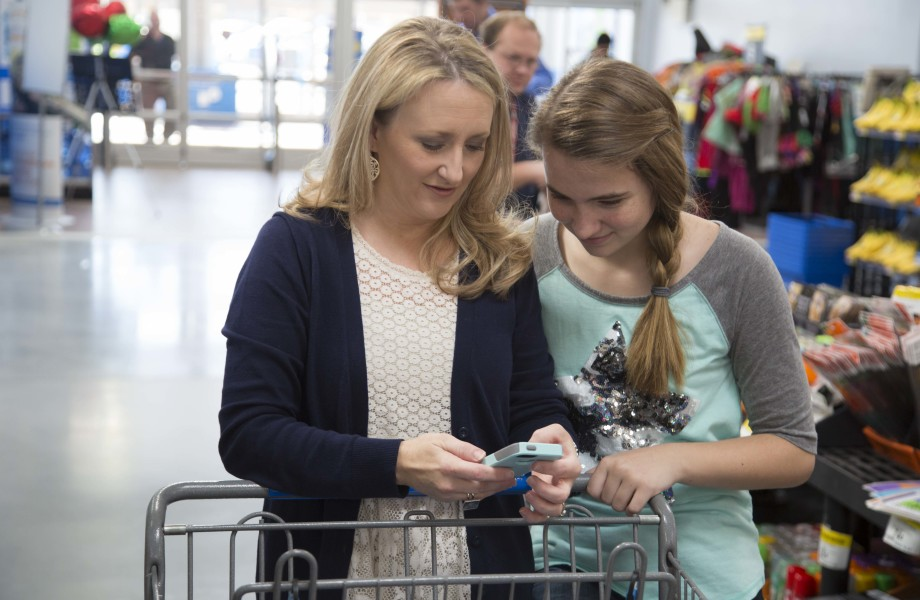 Customers use a smartphone in a Walmart store