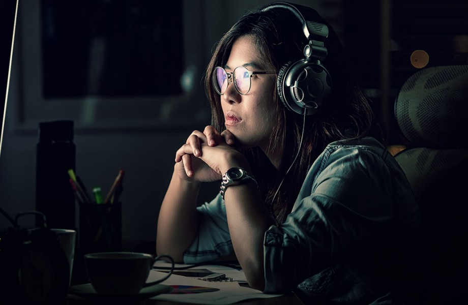 A woman looks at a computer while wearing headphones