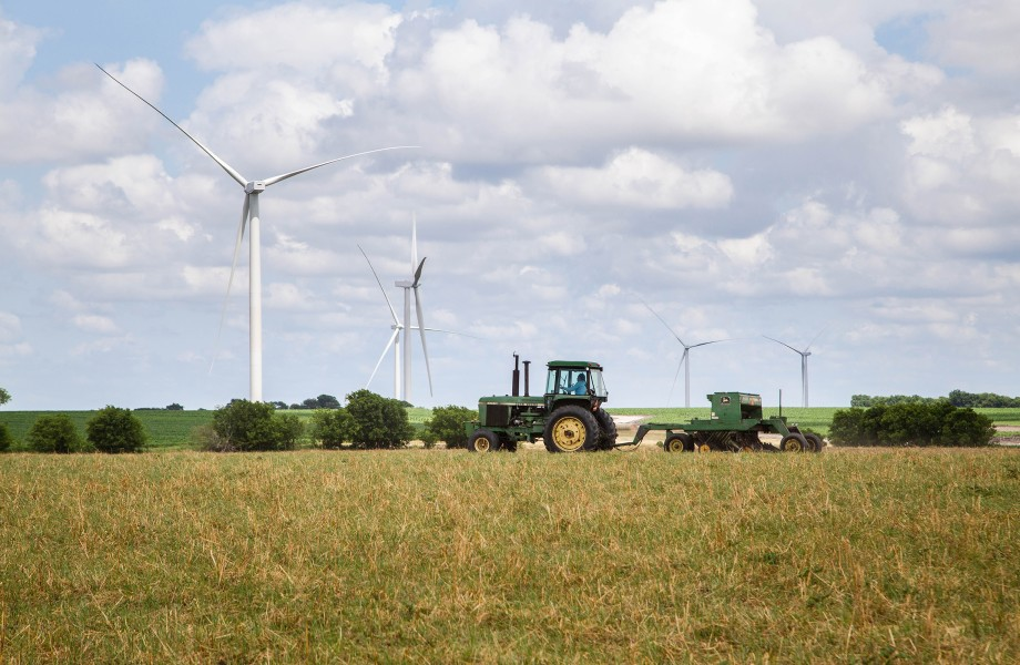 Tractor in field with windmill farm in background
