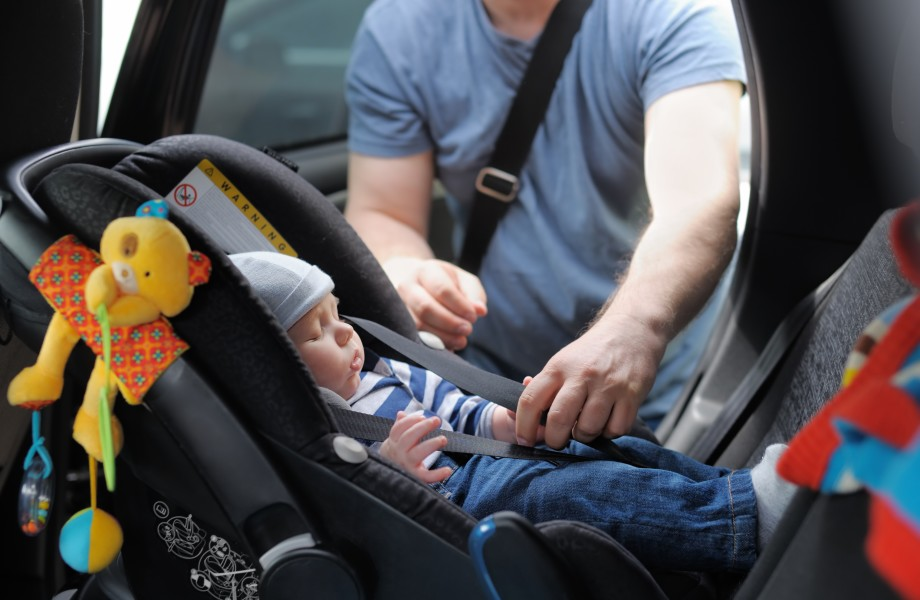 Adult buckling child in car seat