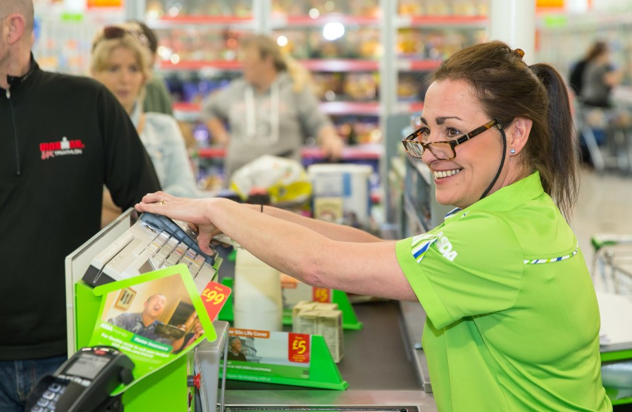 A female colleague is assisting customers at the checkout