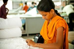 A woman is handling fabric in a manufacturing plant
