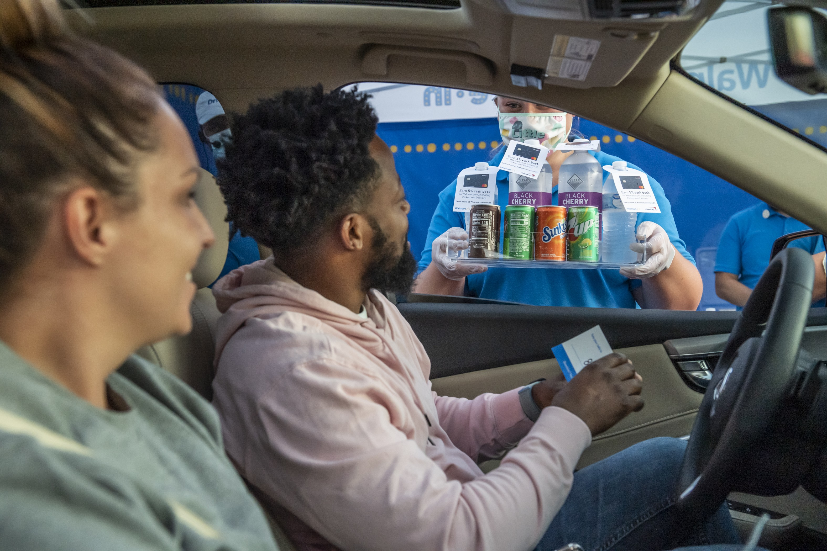Walmart Drive-In associate passing out drinks to customers