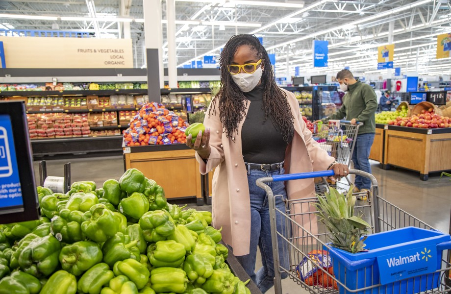A masked customer inspects a bell pepper in the produce section