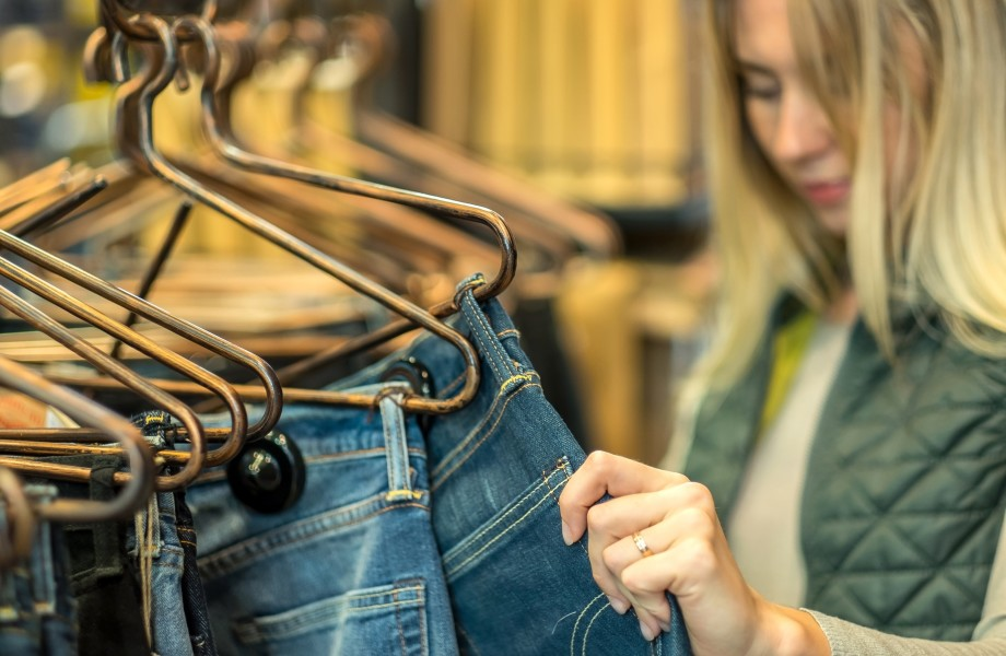 Woman shopping and looking at jeans on hangers