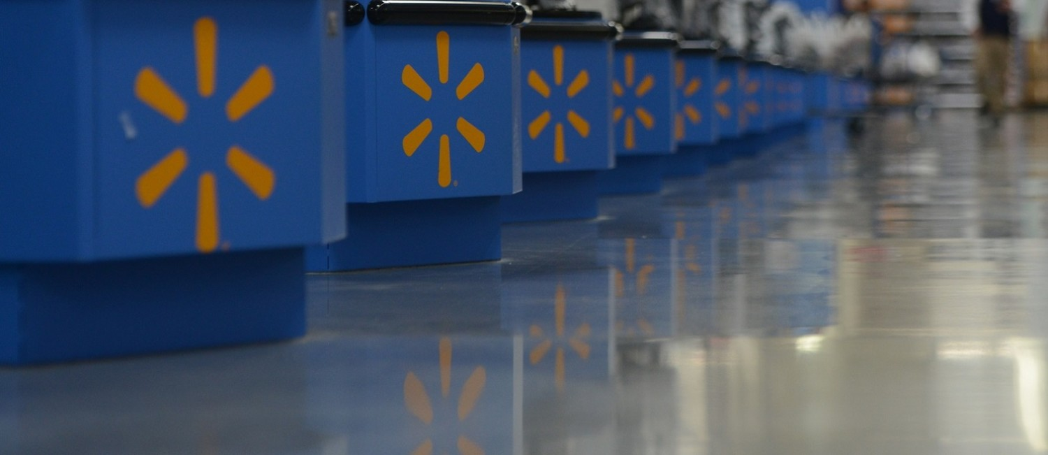 A long line of blue registers with Walmart's spark are stocked with empty plastic shopping bags. Two customers walk past the registers pushing their recently purchased items.