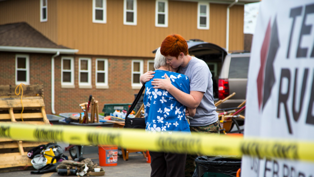 Two people hug after a natural disaster