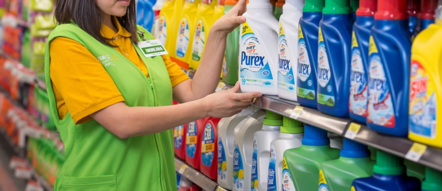 Walmart Associate Andreana wears a bright green vest and places a white Purex bottle on a shelf