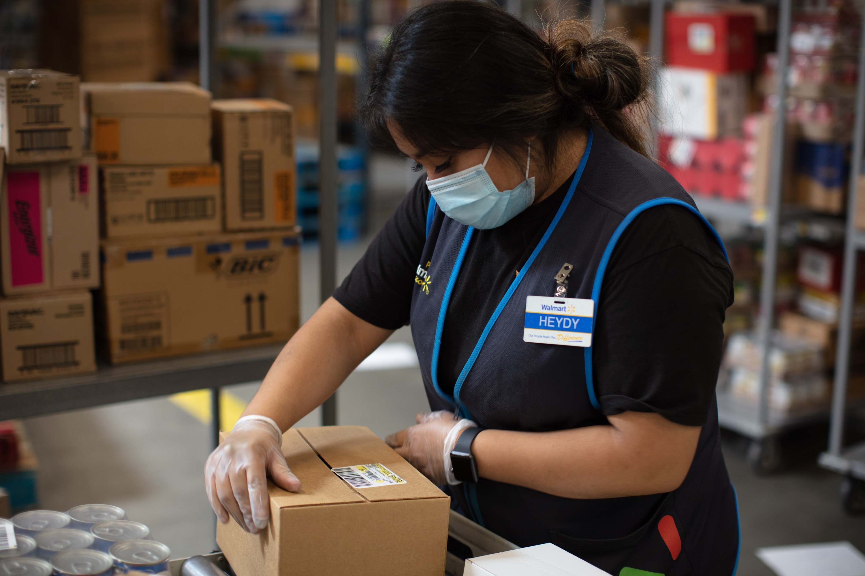 Heydy, a Walmart associate, wears a mask while unloading boxes