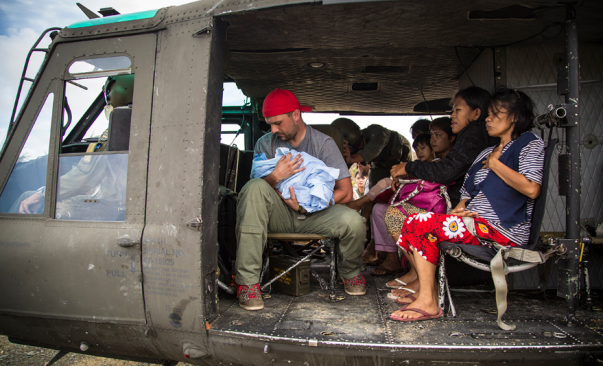 A Team Rubicon worker holds a swaddled infant next to a young family in a helicopter