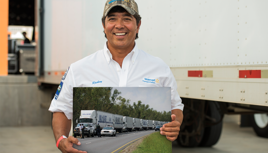 A man proudly holds a 2005 image of Walmart trucks waiting to enter affected areas of the Gulf Coast after Hurricane Katrina