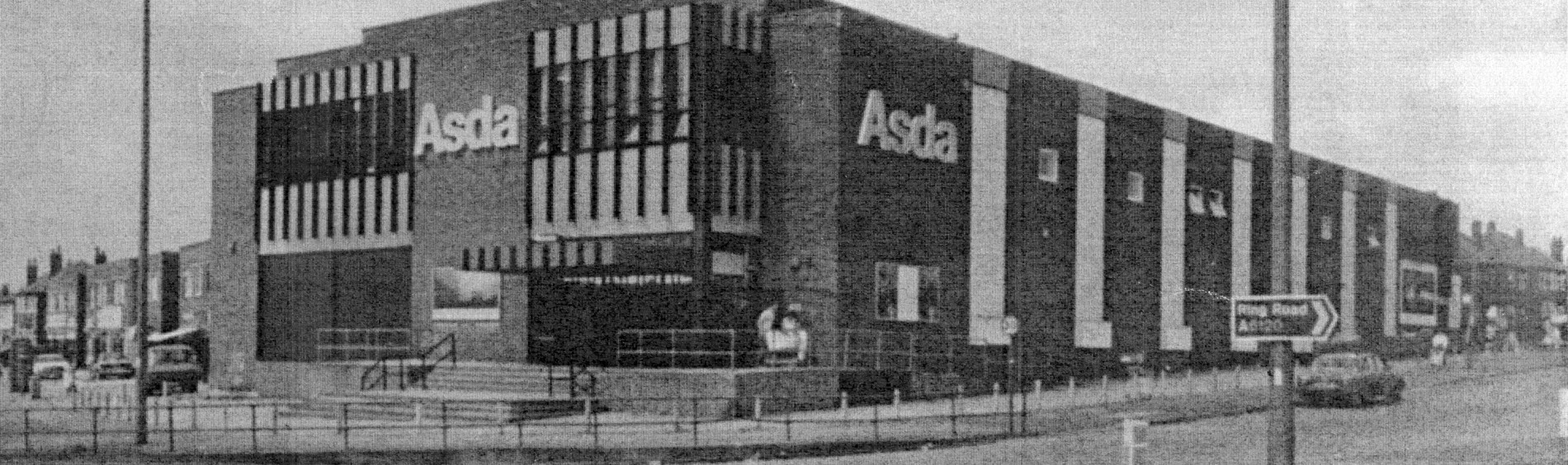 Black and white image of a two story brick building with ASDA logo on side and front