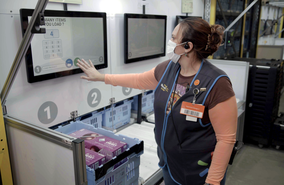 Walmart associate interacting with screen in a local fulfillment center