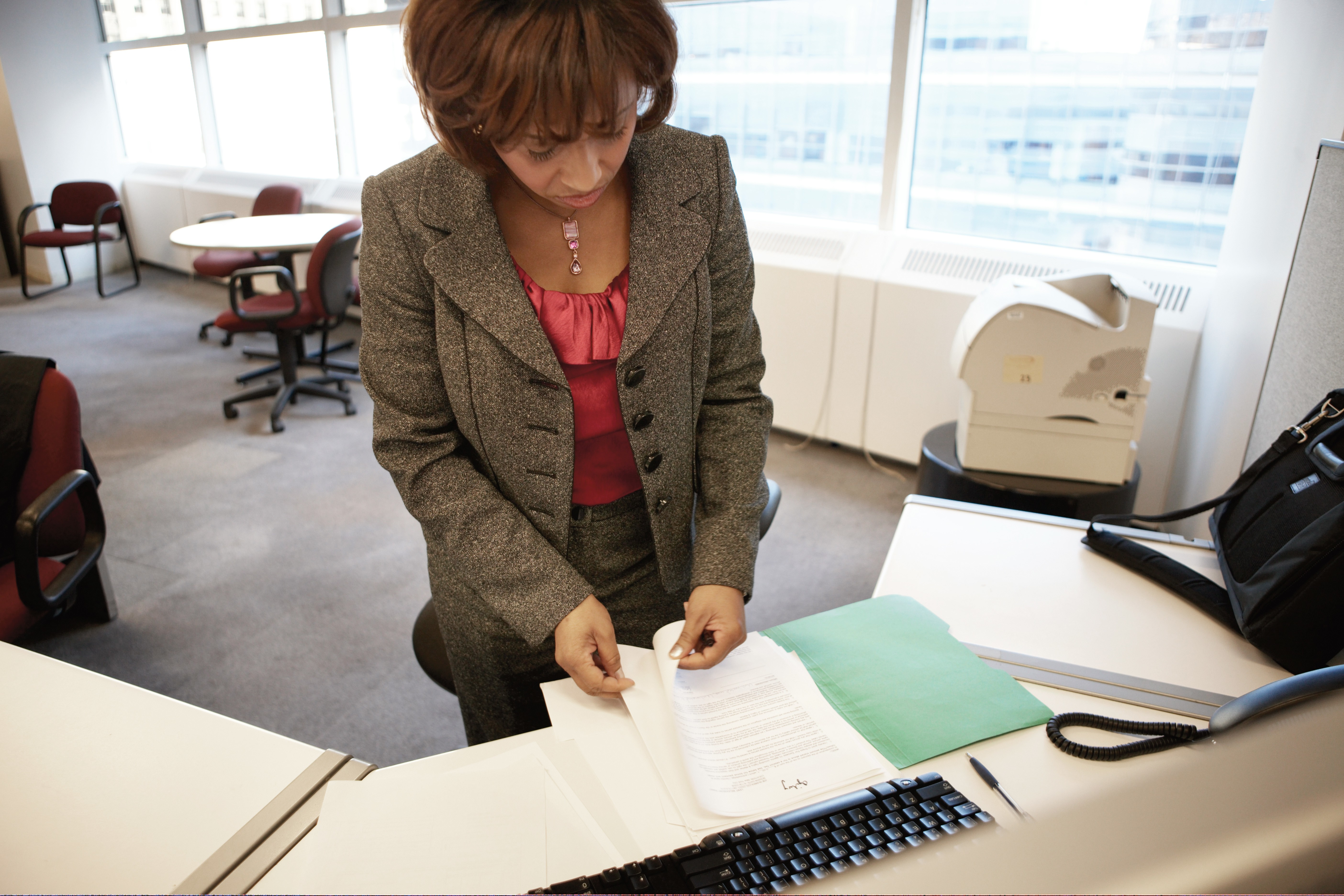 Woman Standing at Desk Looking Through Papers