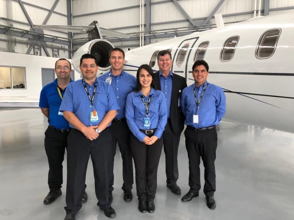 Walmart Aviation associates smile next to a plane