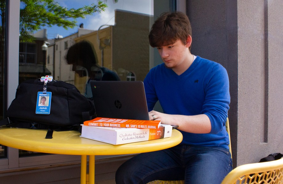 Associate sitting outside at a table studying on laptop with badge hanging off book bag