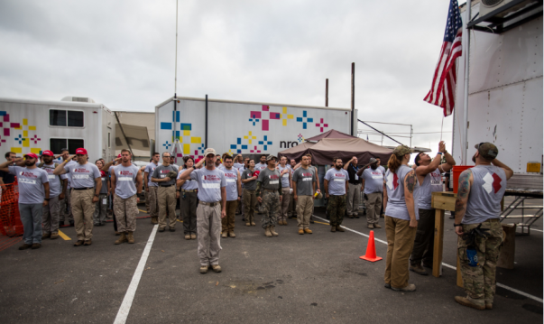 An American flag is raise and saluted by a large group of Team Rubicon members
