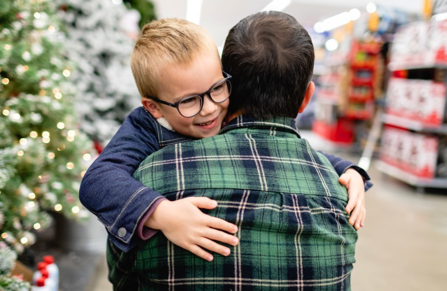 Customer carrying boy with Christmas Trees in aisle