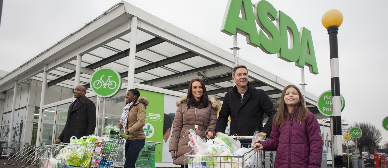 A family leaves an ASDA store with a cart full of items