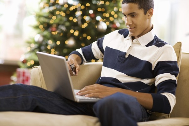 Man shopping online on laptop in front of a Christmas tree