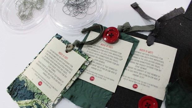three scarves made of recycled textiles with a tag fastened on with a red button