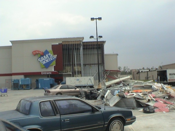 The majority of the exterior of a Sam's Club is ripped a part and the rubble is piled together in a parking lot