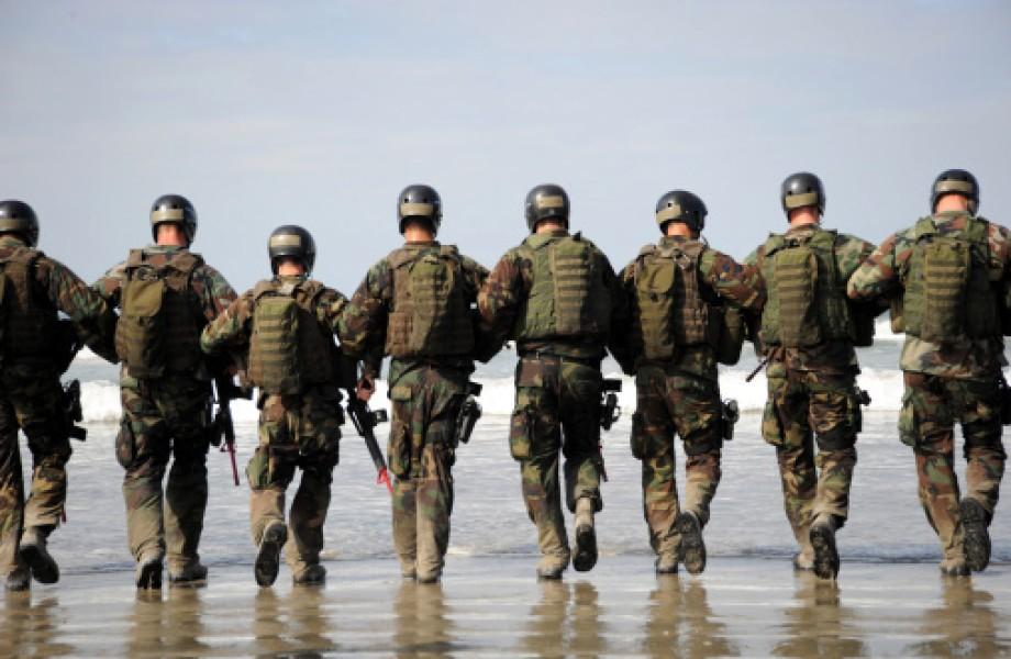Eight soldiers with camo gear walk with their arms linked together on a beach towards the ocean.