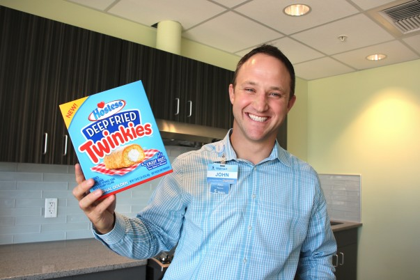 A male associate smiling with a box of deep fried twinkies