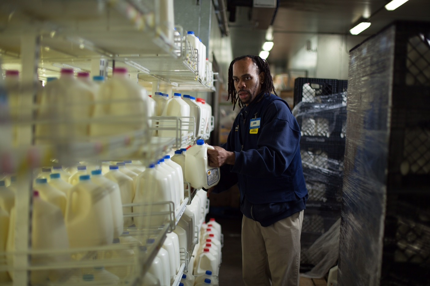 John Geeter grabs a gallon of milk from a shelf in a Walmart dairy department back room