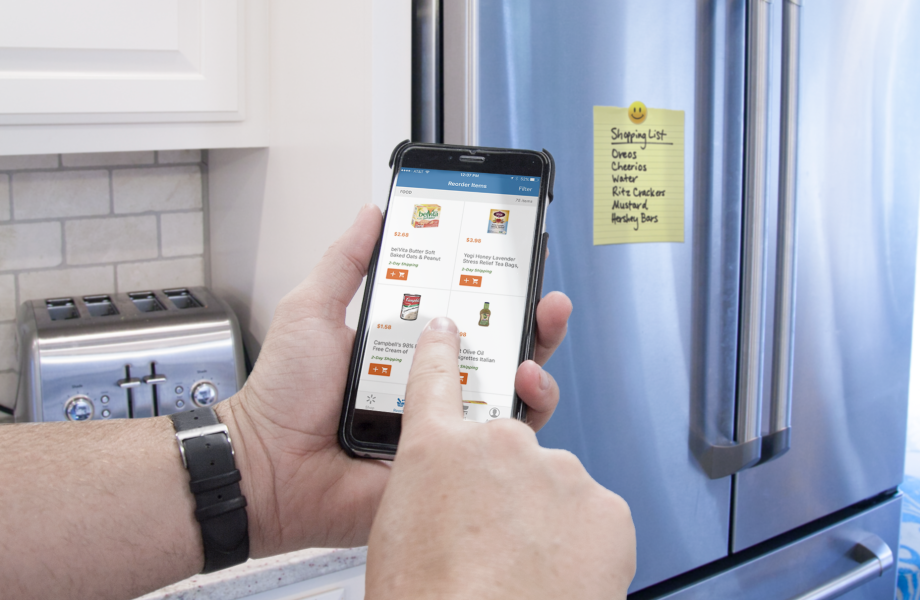 Using a cell phone in front of a refrigerator with a grocery list on it