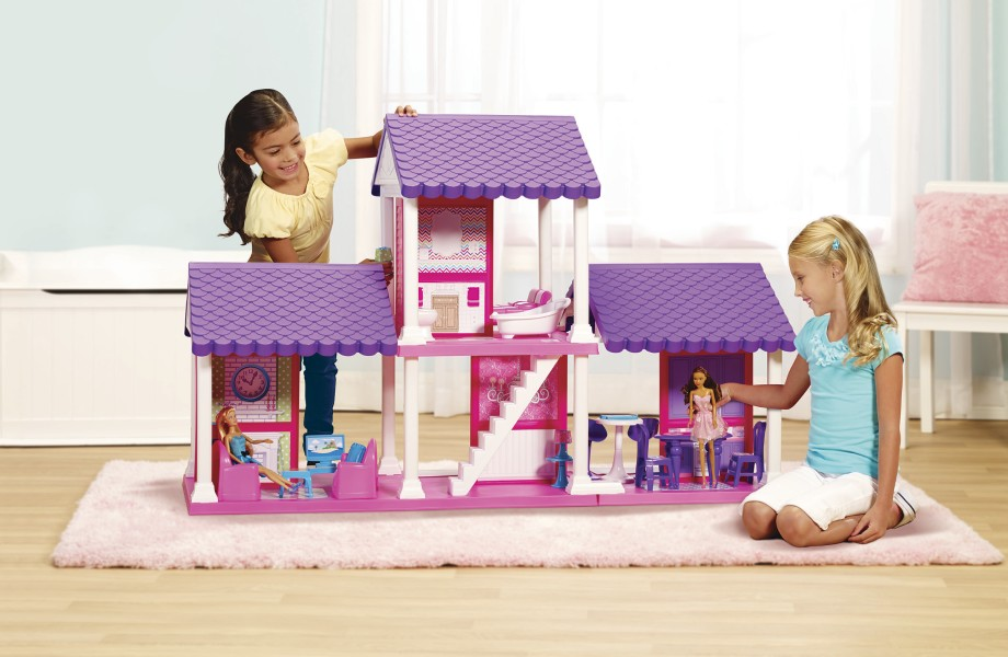 Two young girls are playing with pink and purple dollhouse in a bedroom