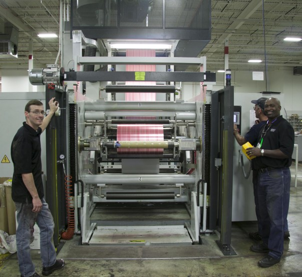 Pressmen are standing beside a at the wrapping paper machine