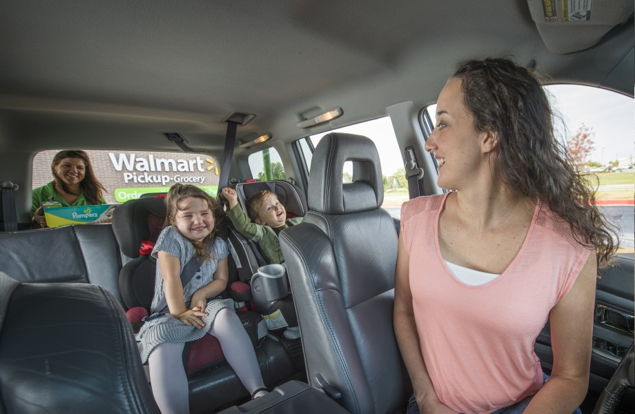 A female customer and two children wait while their groceries are loaded into a vehicle