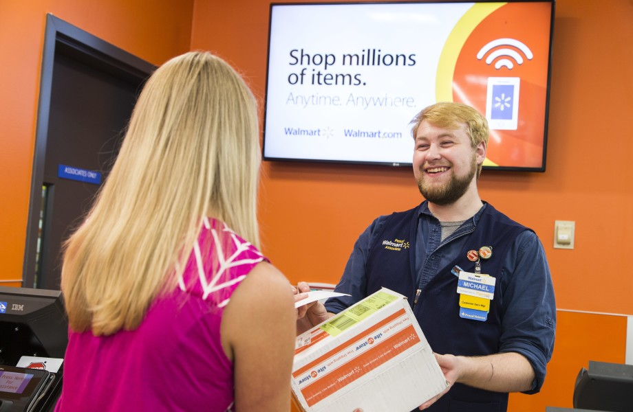 Pick up associate hands a customer her walmart.com order